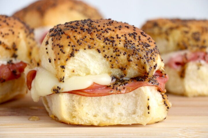 ham and cheese sliders with seeds on the top bun on top of a wooden cutting board.