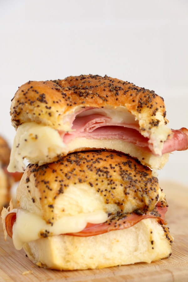 two air fryer ham and cheese sliders stacked on top of one another. top slider is missing a bite.