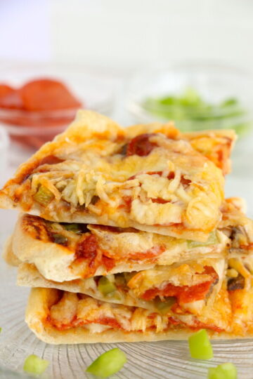 Closeup shot of pizza slices stacked ato one another on plate