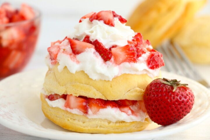 Air Fryer Strawberry Shortcake on a white plate with a strawberry in front of the shortcake.