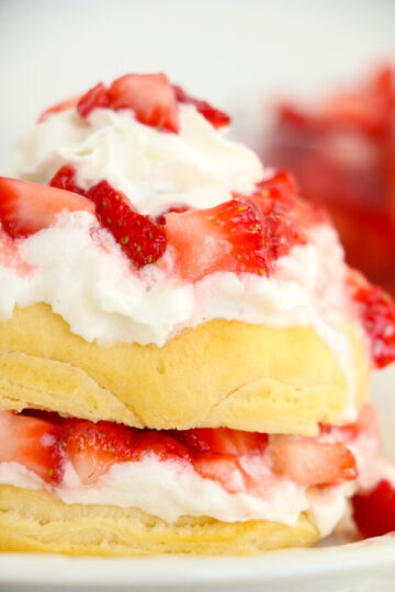 close up of air fryer strawberry shortcake on a white plate, with whipped cream.
