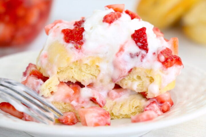 strawberry shortcake with biscuits, topped with sliced strawberries and whipped cream on a white plate
