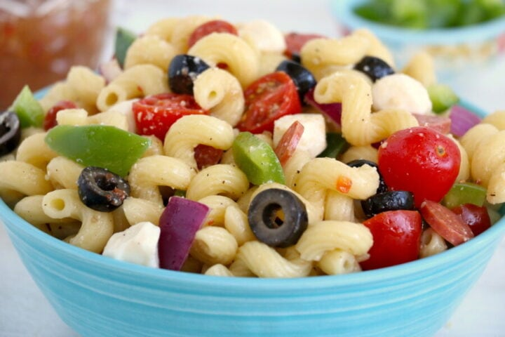 close up of pasta salad in a light blue serving bowl.