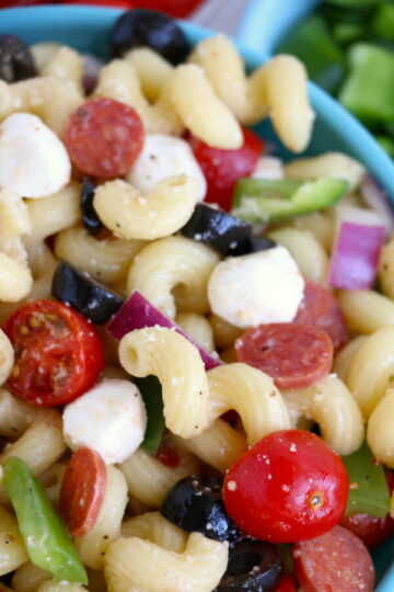 close up off center image of italian pasta salad in a light blue bowl.