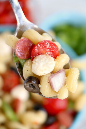 close up image of a sliver spoon full of italian pasta salad.