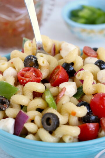 close up vertical image of a bowl of classic pasta salad with a sliver spoon in the background of the bowl.