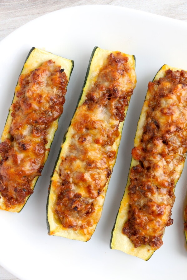 Overhead shot of stuffed zucchini boats with ground beef on white plate