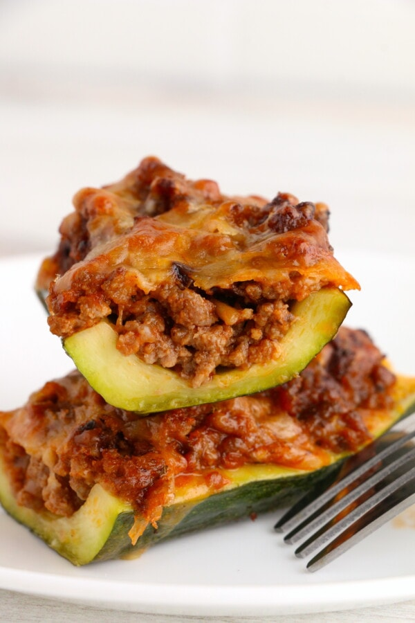 Closeup shot of stuffed zucchini boats with ground beef stacked atop one another on white plate