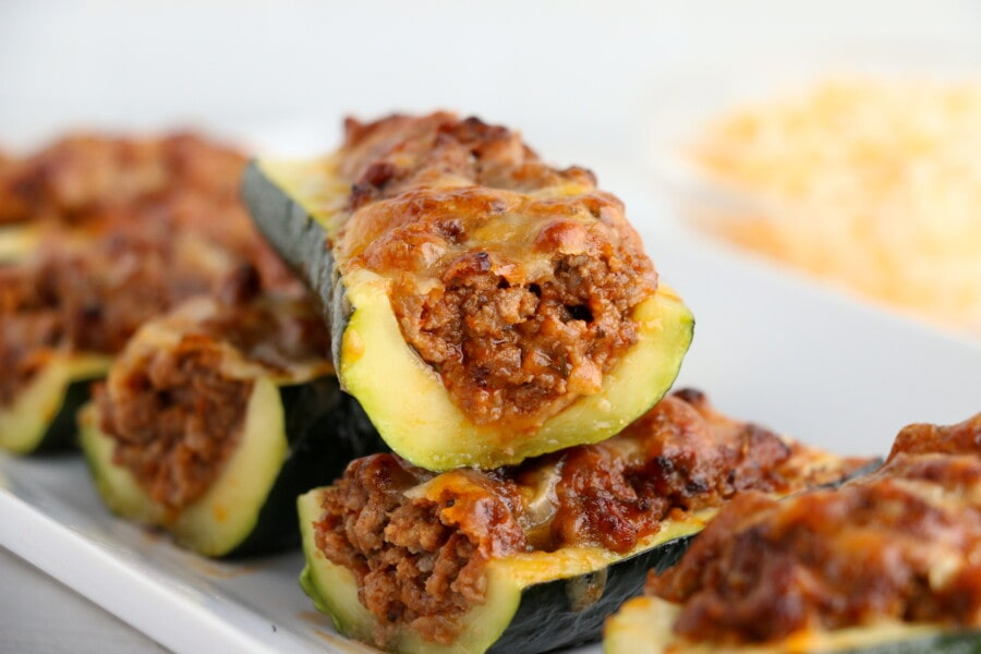 Closeup shot of zucchini stuffed with meat sauce on white plate