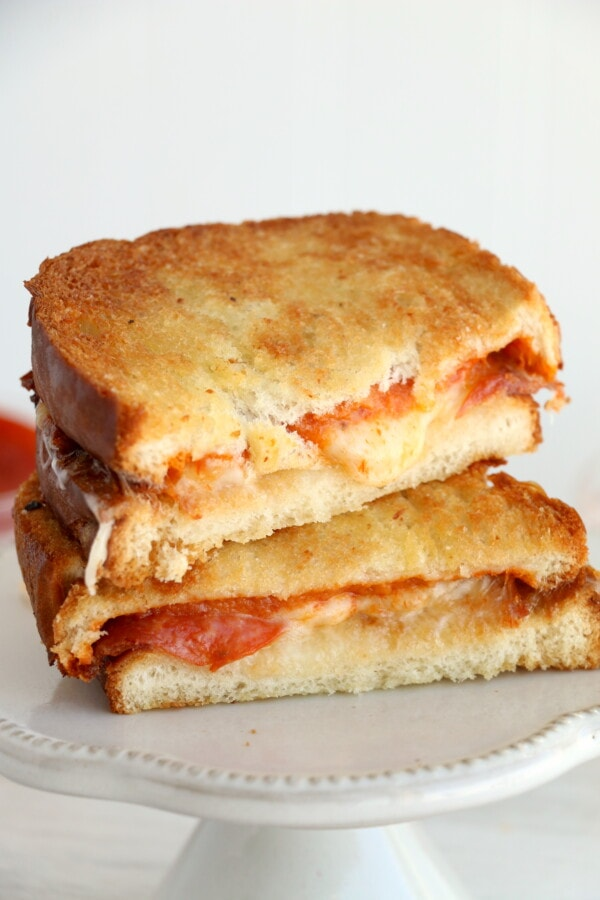 Closeup shot of air fryer grilled cheese sandwich halves stacked atop one another on white plate.