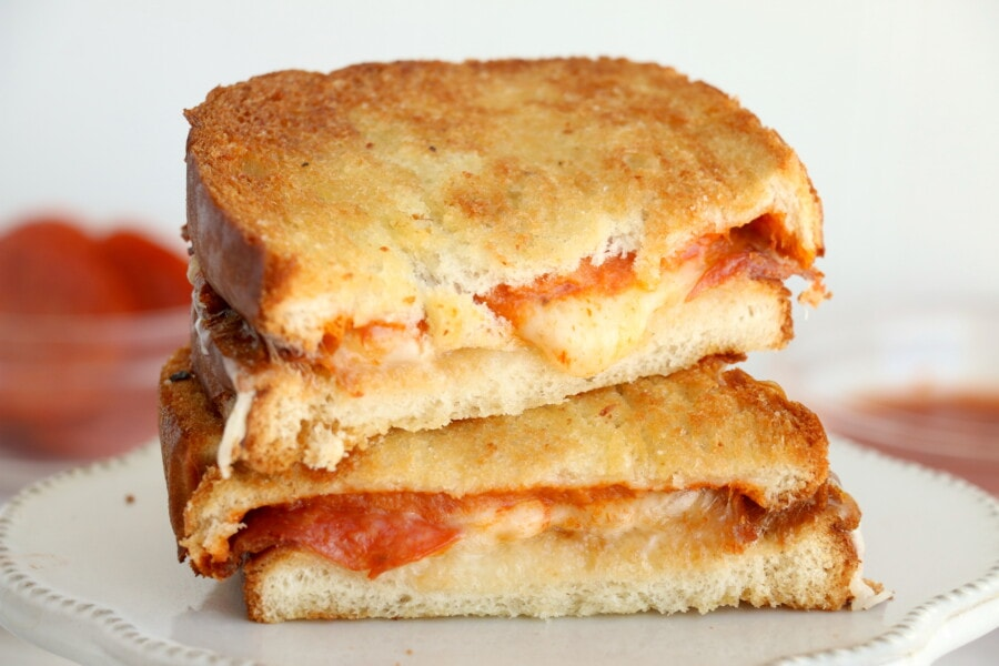 Air fryer pizza grilled cheese sandwich halves stacked atop one another on white plate