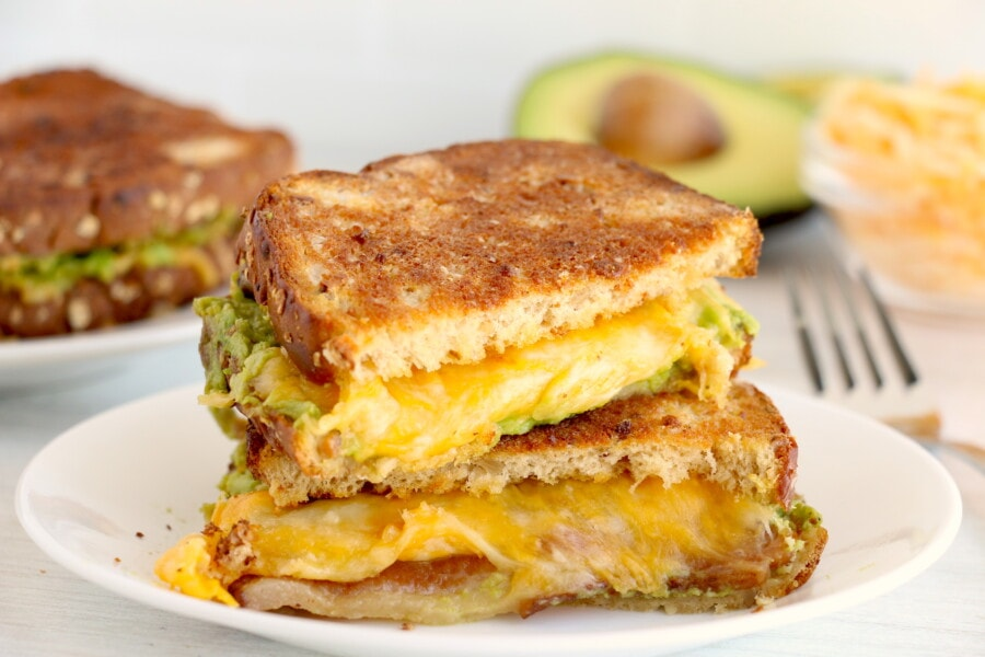 Two halves of air fryer grilled cheese sandwich stacked atop one another on white plate with another bacon avocado grilled cheese in background