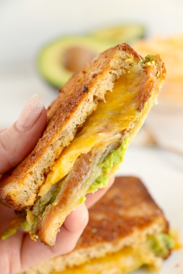 Closeup shot of hand holding a slice of air fried grilled cheese sandwich with remaining bacon avocado grilled cheese below