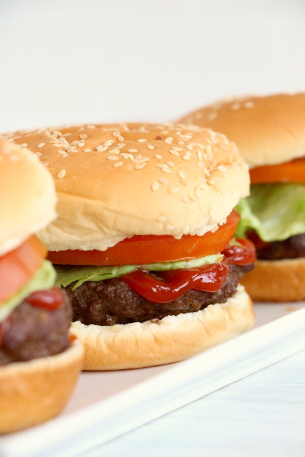 Close up shot of air fryer hamburgers on buns on white plate