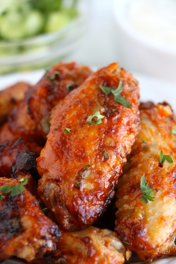 Closeup shot of air fryer buffalo chicken wings stacked atop on another on white plate