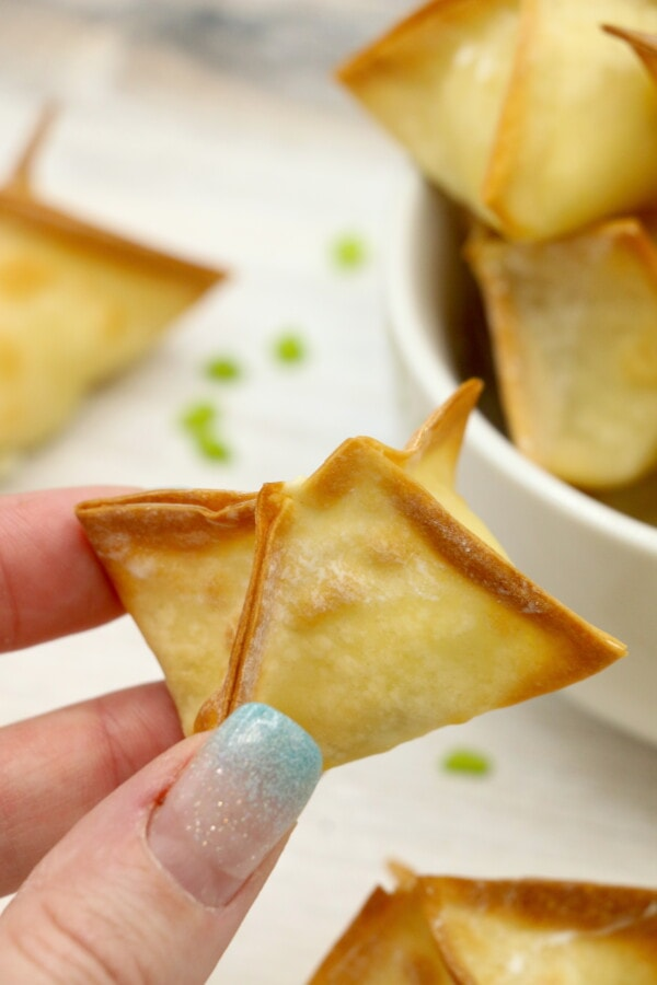 air fried cream cheese stuffed wrapper cooked crispy. held in a women's fingers with glittery blue tipped nails.
