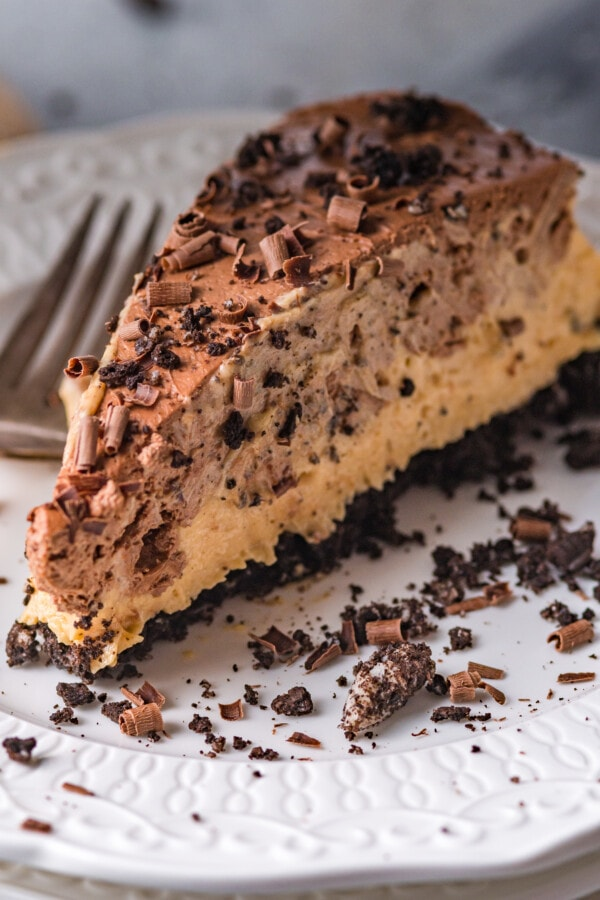 Closeup shot of slice of no bake chocolate peanut butter pie on white plate