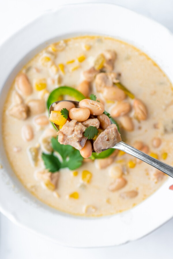 Closeup shot of spoonful of slow cooker white chicken chili with more chili in bowl below