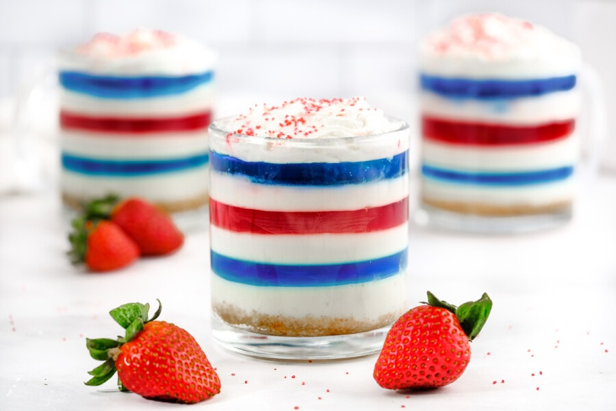 Layered jello cake in shooter glasses with fresh strawberries on table