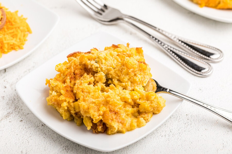 Cheesy sweet corn casserole on white plate with fork. One of the best side dishes for ham.