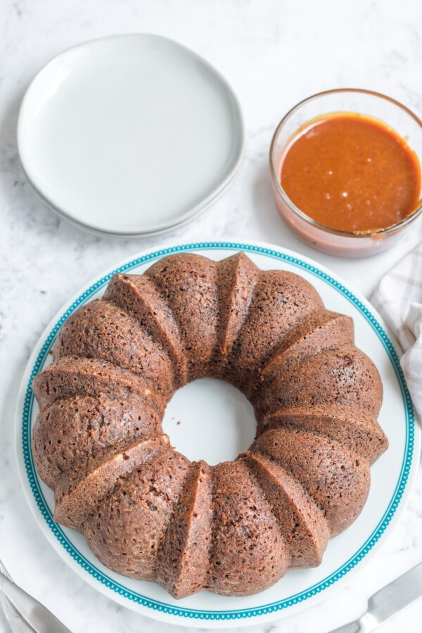 A baked caramel apple Bundt cake is the main focus of this image, with serving plates and caramel sauce also pictured