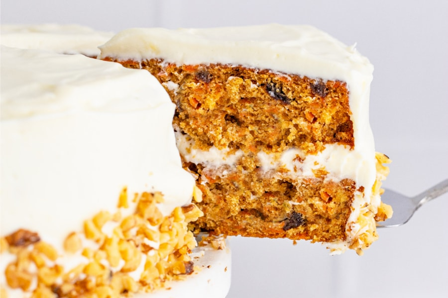 Closeup shot of slice of layered carrot cake being cut out of cake