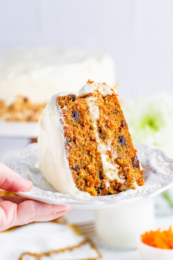 Hand holding white plate with slice of carrot cake on it