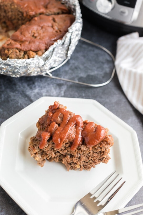 Piece of instant pot meatloaf on white plate with more meatloaf in background