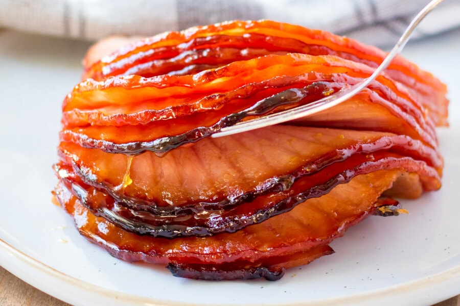 Boneless spiral ham with fork on white plate