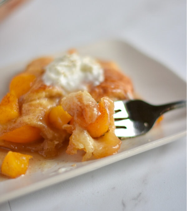 Fork holding a bite of peach cobbler on a white plate with whipped cream.