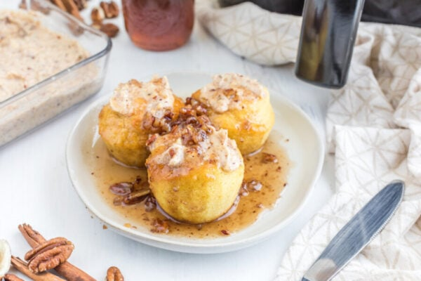 plate of air fryer pancake muffins with syrup and dollaps of flavored butter