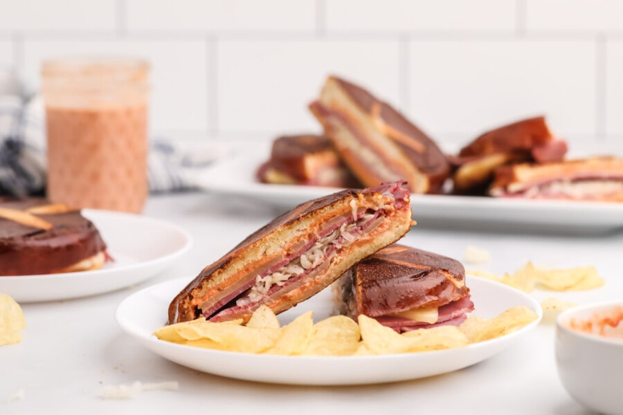 Toasted Reuben sandwich slices with chips on white plate.