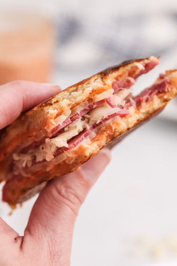 Closeup shot of hand holding toasted Reuben sandwich with chipotle aioli sauce