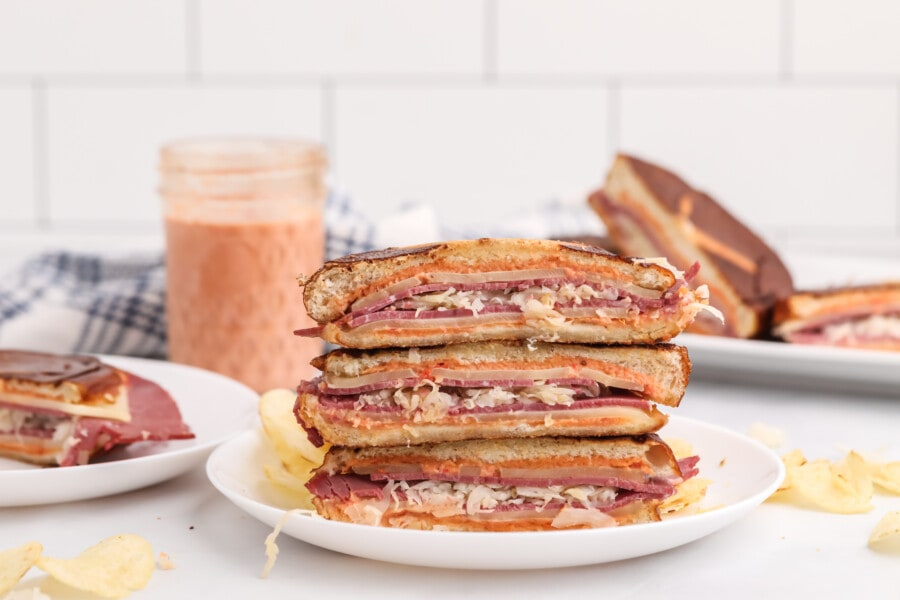 Toasted Reuben sandwich halves with chipotel aioli sauce stacked atop one another on white plate with more sandwiches in background