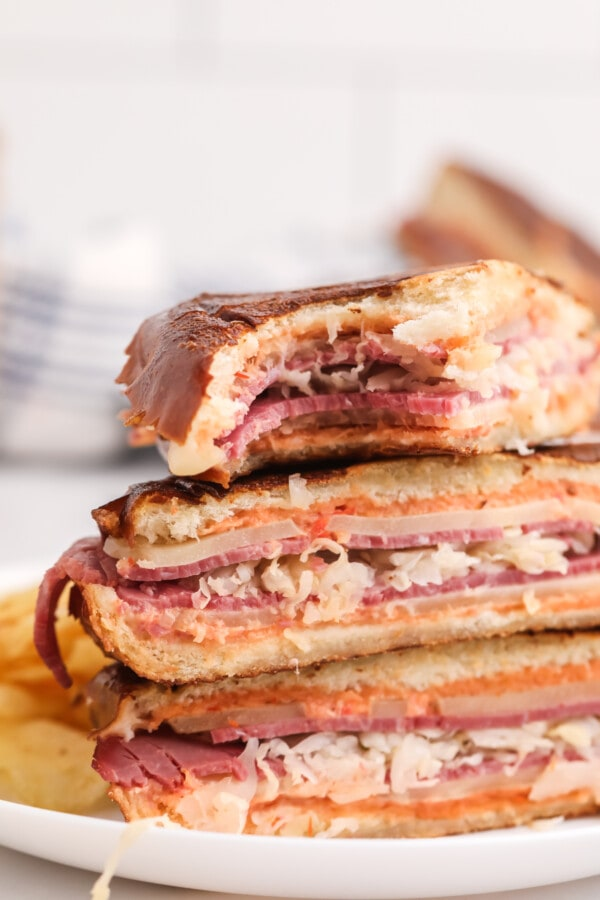 Closeup shot of pressed toasted Reuben sandwich halves on white plate