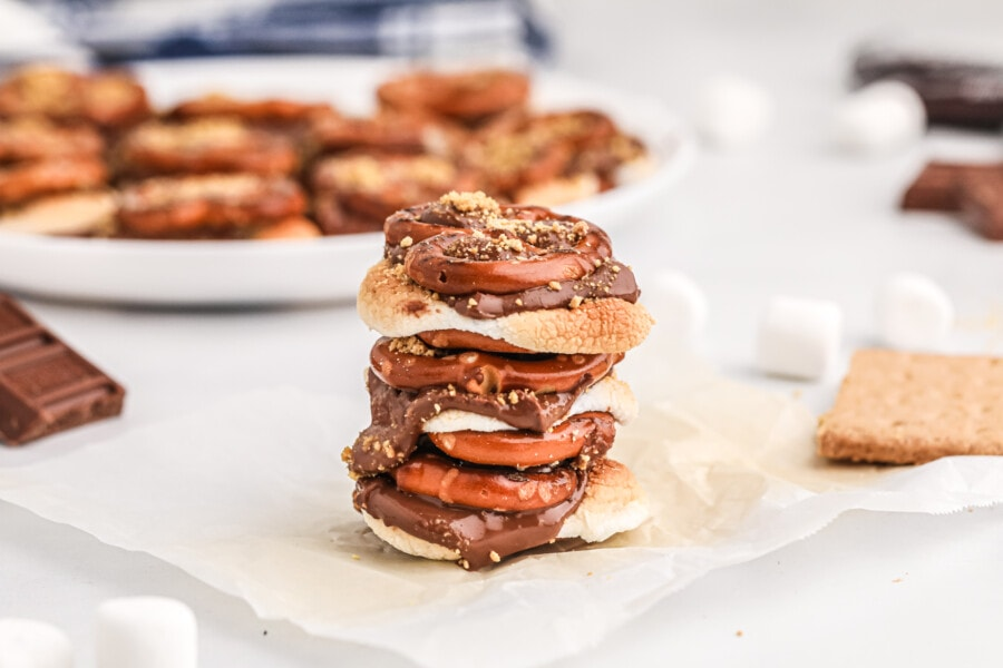 Stack of pretzel s'mores bites on parchment paper with more in background on plate