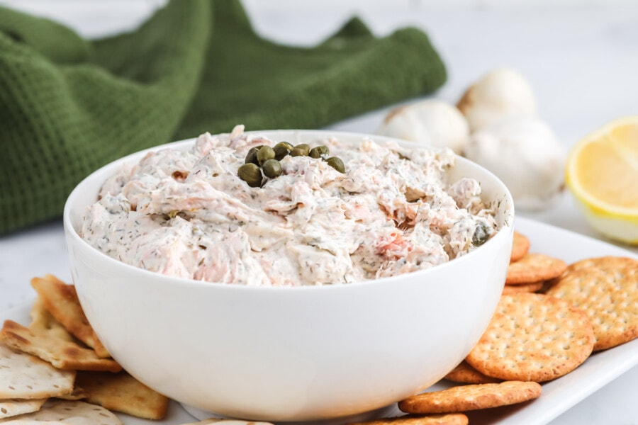 A white bowl filled with smoked salmon dip and a pinch of capers with a green towel, raw garlic and a fresh lemon in the background.