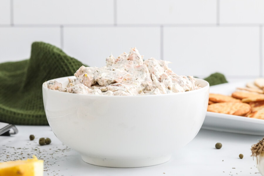 A side picture of the white bowl full of smoked salmon cream cheese dip and a plate of crackers beside it.