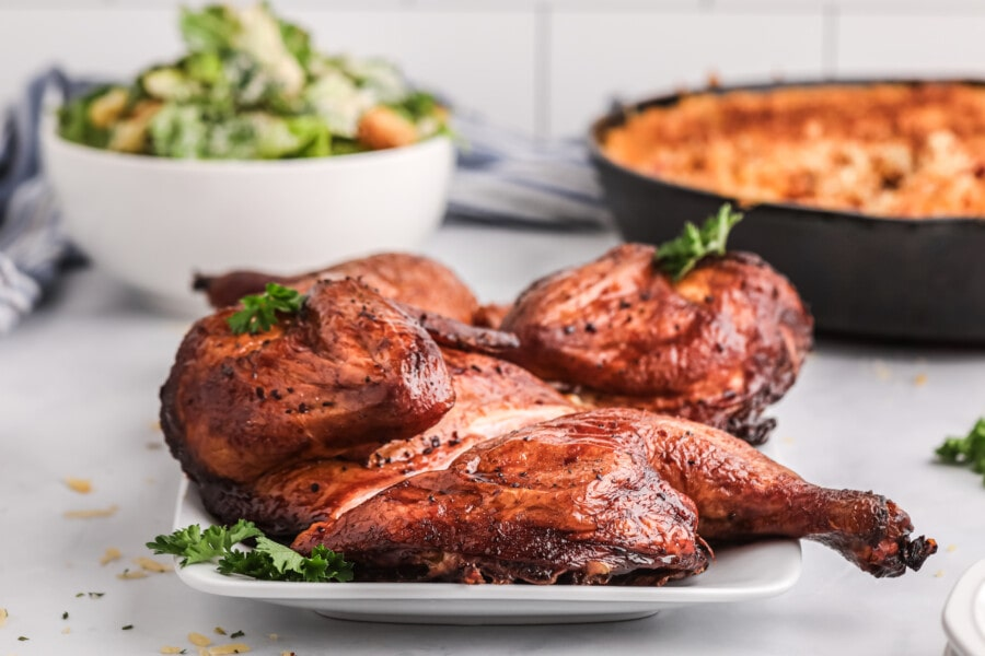 Delcious whole smoked bourbon chicken on white plate