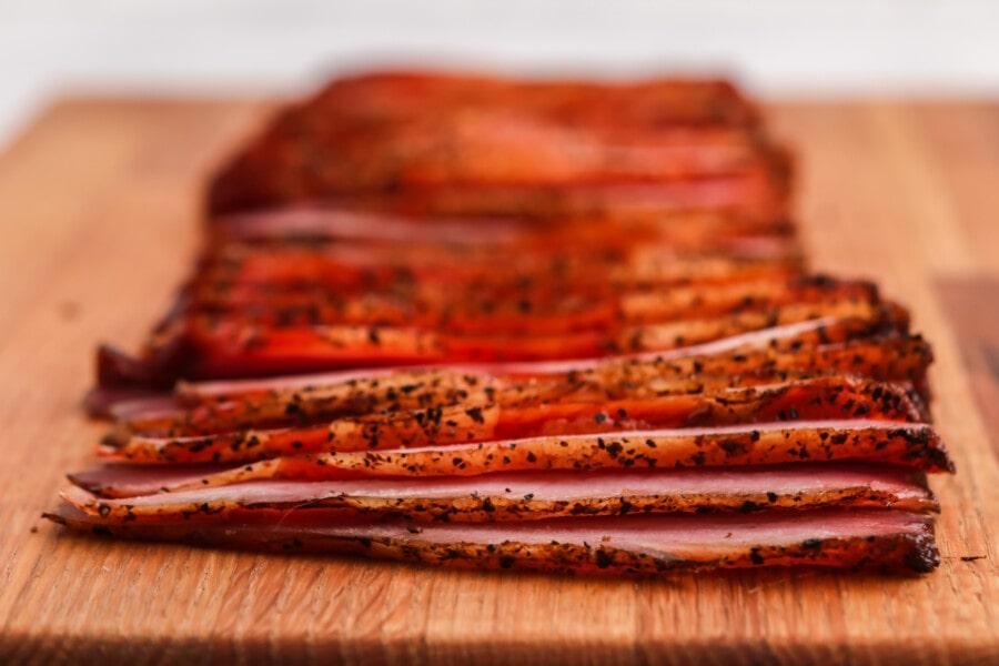 Closeup shot of sliced homemade smoked bacon on cutting board