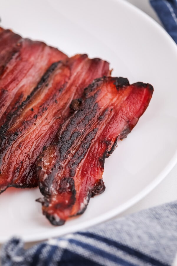 Slices of cooked homemade smoked bacon on white plate