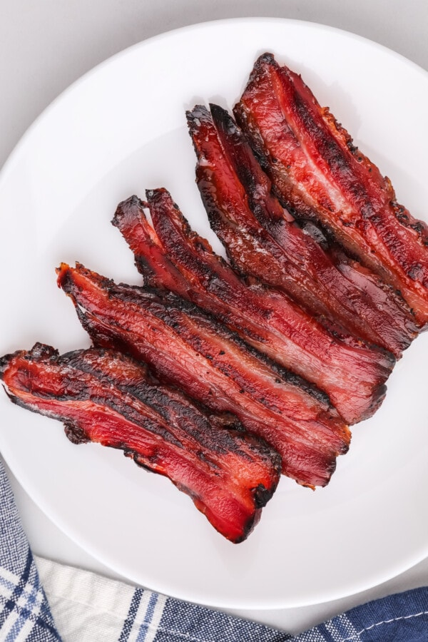 Overhead shot of slices of smoked pork belly bacon on white plate