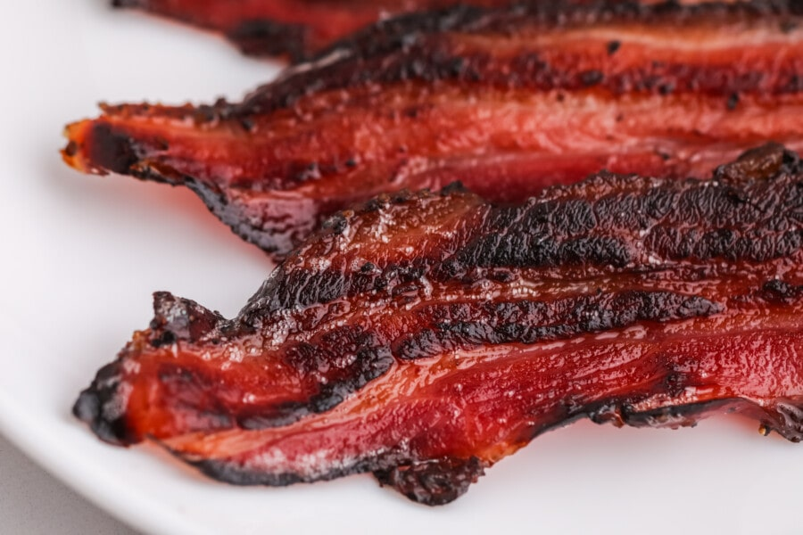 Closeup detail shot of fried maple smoked bacon on white plate