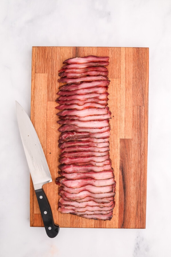 Overhead shot of butcher knife next to smoked bacon on cutting board