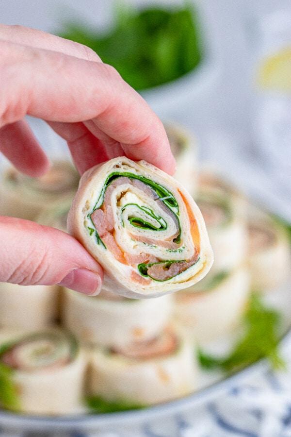 Closeup shot of hand holwing salmon pinwheel with more easy smoked salmon pinwheels in background