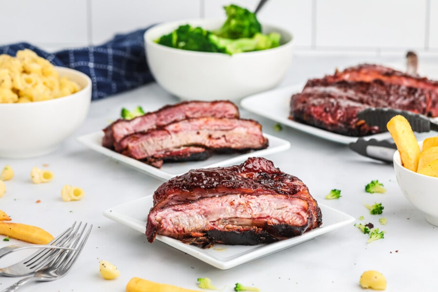 Three white plates with St. louis ribs with bowl of macaroni and cheese and broccoli in background