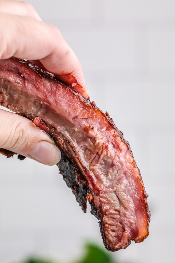 Closeup shot of hand holding St. Louis style spare ribs
