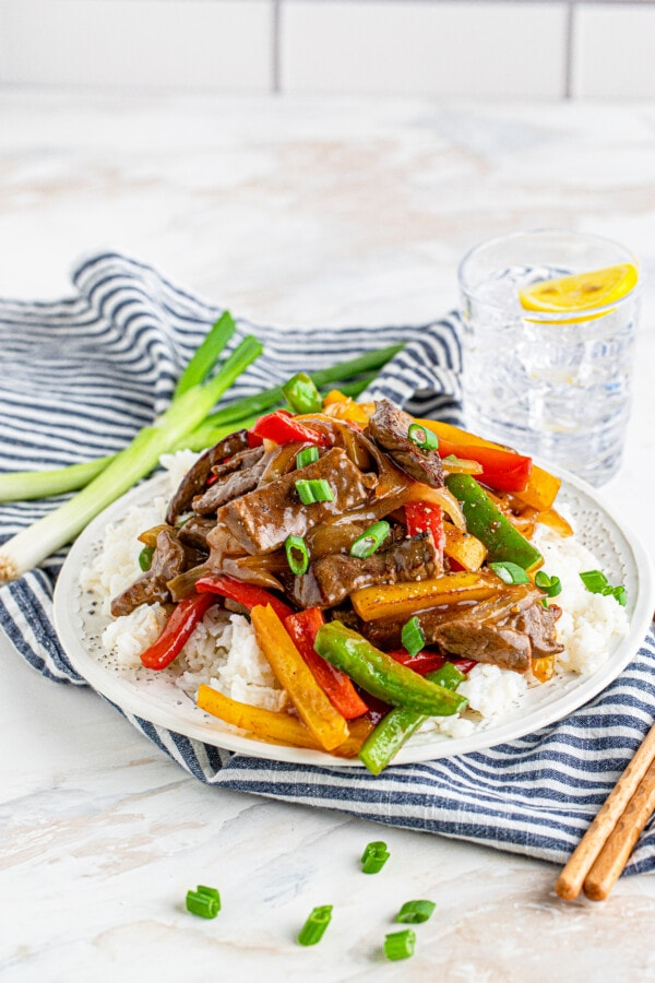 Simple steak or chicken and peppers stir fry over rice on white plate