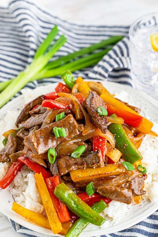 Steak or chicken and peppers stir fry over rice on white plate