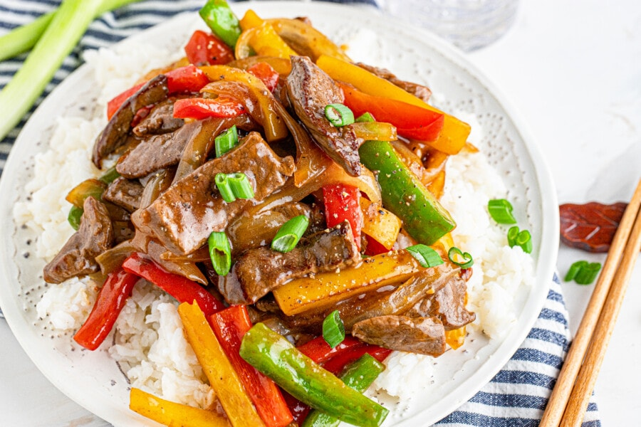 Simple steak and pepper stir fry on bed of rice on white plate